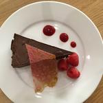 Rich chocolate torte with raspberry coulis and a black pepper tuille