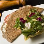 Crêpe de sarrasin aux saveurs diverses viandes charcuterie ou végetariennes accompagnés d'une panière de parmesan grillés et mélange vert