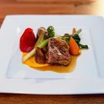 Selle d'agneau rôtie aux aromates, piquillos farci d'un navarin et petits légumes au jus court