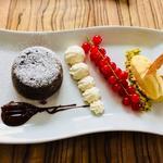 Coulant aux chocolat noir 80% avec sa crème chantilly et boule de glace vanille sur une brunoise de pistache de Bronte