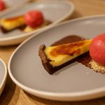 Caramelised lemon tart with chocolate and almond crust served with raspberry sorbet