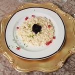 Anchovies flavoured butter risotto topped with caviar, pomegranate seeds and lime
