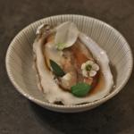 En amuse-bouche : Huître d'Arcachon prise en gelée de bouillon daïshi, fleur de ciboule de Chine